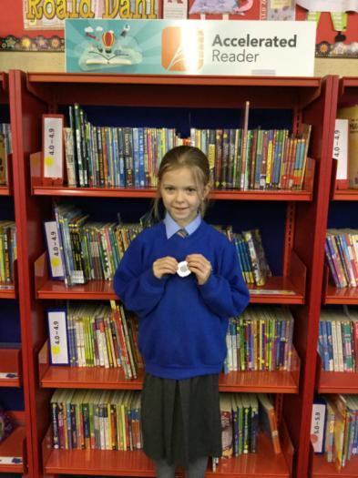 Dearbhaile with her special reading medal for making great progress in her reading.