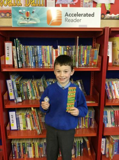 Niall Burt with his special reading medal for making excellent progress in his reading.