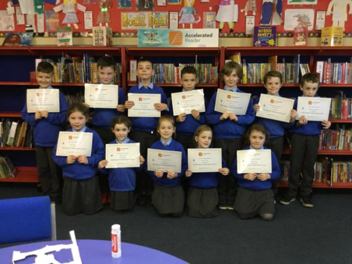 Primary 4 pupils in P4UB proudly display their reading certificates.
